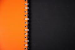 Cubierta del cuaderno y fondo de la pizarra imagenes de archivo