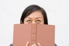 Cubierta del estudiante su cara con el libro Imágenes de archivo libres de regalías