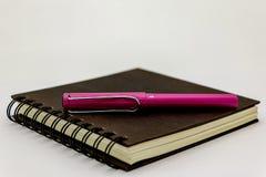 Cubierta del negro del cuaderno y pluma rosada Foto de archivo