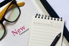 Cubierta del nuevo testamento en Sagrada Biblia con el cuaderno, la pluma y los vidrios fotografía de archivo libre de regalías