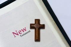 Cubierta del nuevo testamento en Sagrada Biblia con una cruz de madera fotografía de archivo libre de regalías