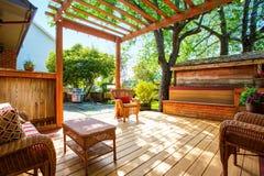 Cubierta del patio trasero con muebles y la pérgola de mimbre imagen de archivo libre de regalías