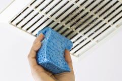Cubierta del respiradero de la fan del cuarto de baño de la limpieza con la esponja imagen de archivo libre de regalías