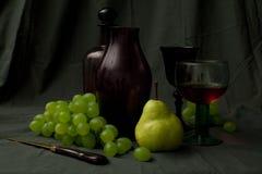 Cubierta exquisita con la garrafa, el vidrio y las uvas Imagenes de archivo