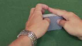 Cubierta masculina de la barajadura de las manos de las tarjetas del póker almacen de video