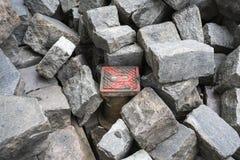 Cubierta pintada de la alcantarilla en el medio de piedras del adoquín Foto de archivo libre de regalías