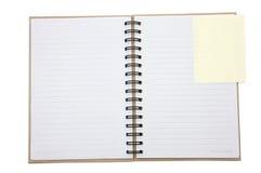 Cubierta reciclada del cuaderno abierta con recordatorio amarillo foto de archivo