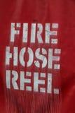 Cubierta roja del carrete de la manguera de bomberos con la escritura Fotos de archivo libres de regalías