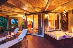 Cubierta romántica en hogar tropical con la bañera y las velas Foto de archivo libre de regalías