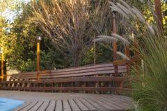 Cubierta y banco de madera por la piscina Imagen de archivo