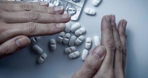 Cubiertas de las manos y ocultación de muchos medicamentos de venta con receta, tabletas de la medicina o píldoras blancas de la  metrajes