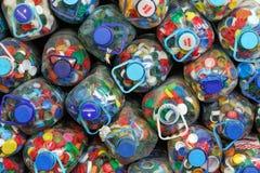Cubiertas plásticas coloreadas en botellas plásticas en la fábrica en el proceso de las materias primas secundarias fotografía de archivo libre de regalías