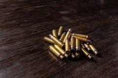 Cubiertas vac?as de la bala en una tabla oscura, de madera imágenes de archivo libres de regalías