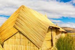 Cubierto con paja a casa en las islas flotantes en el lago Titicaca Puno, Perú, Suramérica. La raíz densa que planta a Khili entre Foto de archivo