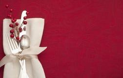 Cubierto de la Navidad con Sterling Silverware en la servilleta y la cinta blancas en fondo rojo con el espacio de la copia o siti Fotos de archivo