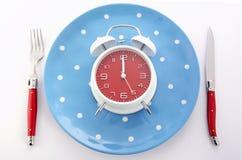 Cubierto de la tabla de la hora de comer con el despertador imagen de archivo