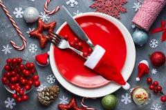 Cubierto de la tabla de la Navidad con la placa roja, cubiertos en santa h Foto de archivo libre de regalías