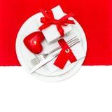 Cubierto de la tabla del día de tarjetas del día de San Valentín en rojo y blanco con la vela Imágenes de archivo libres de regalías