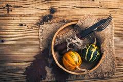 Cubierto rústico del otoño con las calabazas miniatura en un rústico Imagen de archivo libre de regalías