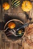 Cubierto rústico del otoño con las calabazas miniatura en un rústico Foto de archivo