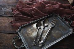 Cubiertos de la cocina del vintage - cucharas y bifurcación en la bandeja de plata Imagenes de archivo