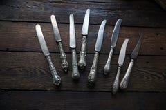 Cubiertos de la cocina del vintage - cuchillos en fondo de madera Imagen de archivo libre de regalías
