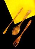 Cubiertos de madera en una servilleta de lino amarilla en fondo negro Foto de archivo libre de regalías