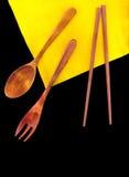 Cubiertos de madera en una servilleta de lino amarilla en fondo negro Imagen de archivo