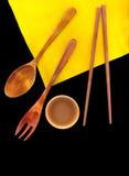 Cubiertos de madera en una servilleta de lino amarilla en fondo negro Fotografía de archivo