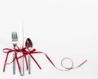 Cubiertos del día de fiesta con la cinta roja Imagen de archivo