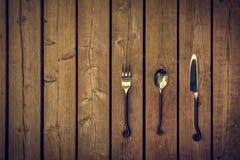 Cubiertos del vintage - bifurcación, cuchara y cuchillo en el fondo de madera Fotos de archivo