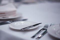 Cubiertos en la tabla blanca Imagen de archivo libre de regalías