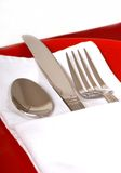 Cubiertos en una servilleta plegable en una placa roja Fotos de archivo libres de regalías