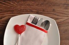 Cubiertos exhibidos en una servilleta blanca con una piruleta roja de la forma del corazón en una placa blanca Imagen de archivo