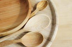 Cubiertos, placas y cucharas de madera en un fondo de madera Visión superior fotos de archivo libres de regalías