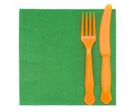 Cubiertos plásticos de la comida campestre en la servilleta verde, servilleta Imágenes de archivo libres de regalías