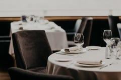 Cubiertos y copas de vino en el mantel blanco, butacas vacías cerca Pasillo del banquete en restaurante Tabla servida para las hu fotos de archivo libres de regalías