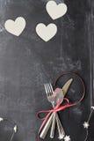 Cubiertos y corazones del día de tarjetas del día de San Valentín sobre la pizarra Imagen de archivo libre de regalías