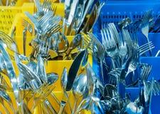 Cubiertos y cubiertos en ocntainer palstic colorido en una cocina industrial del restaurante foto de archivo libre de regalías