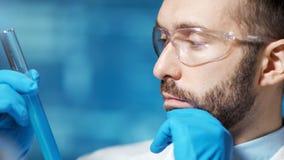 Cubilete masculino tesonero de la tenencia del químico con la sustancia azul que hace experiencia en primer del laboratorio almacen de metraje de vídeo