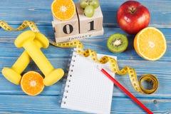 Cubique el calendario con el 1 de enero, las frutas, las pesas de gimnasia y la cinta métrica, Años Nuevos de concepto de las res Fotografía de archivo libre de regalías