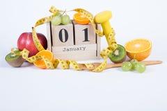 Cubique el calendario con el 1 de enero, las frutas, las pesas de gimnasia y la cinta métrica, Años Nuevos de resoluciones Fotografía de archivo libre de regalías