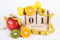 Cubique el calendario con la fecha del 1 de enero, de frutas, de pesas de gimnasia y de la cinta métrica, Años Nuevos de concepto Foto de archivo libre de regalías
