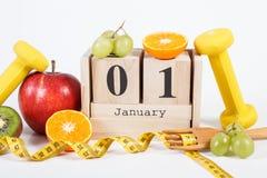 Cubique el calendario con la fecha del 1 de enero, de frutas, de pesas de gimnasia y de la cinta métrica, Años Nuevos de concepto Fotos de archivo libres de regalías