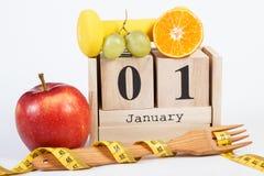 Cubique el calendario, las frutas, las pesas de gimnasia y la cinta métrica, Años Nuevos de resoluciones Imagen de archivo libre de regalías