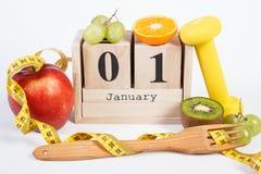 Cubique el calendario, las frutas, las pesas de gimnasia y la cinta métrica, Años Nuevos de resoluciones Fotografía de archivo