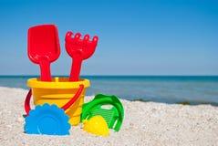 Cubo amarillo del bebé con la manija roja, espátula y rastrillo rojo plástico, y tamiz verde plástico, forma amarilla de la arena Fotos de archivo libres de regalías