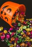 Cubo anaranjado con los chocolates sobre fondo negro Imágenes de archivo libres de regalías