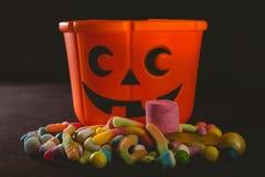 Cubo anaranjado con los diversos caramelos sobre fondo negro Fotografía de archivo