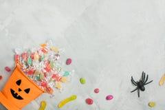 Cubo anaranjado de Halloween con los caramelos, las azufaifas, y la araña de goma Imagen de archivo